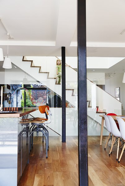 When Molly Alexander and Graeme Anthony were looking for a house to renovate for their growing family—including five-year-old Chloe, seen here—they didn't expect to find it right next door to Alexander's own childhood home. The light-filled sanctuary they created features vintage Singer sewing stools at the American walnut–topped kitchen island and hanging lamps from Ikea.