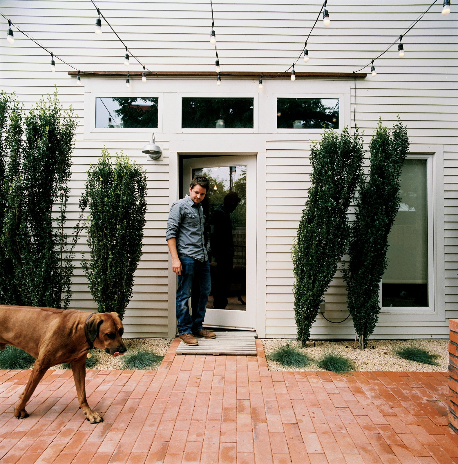 From the side door of his restored two-bedroom bungalow, Dollahite watches his   dog West inspect the newly installed low-maintenance landscaping and brick patio. Tagged: Outdoor, Back Yard, Trees, Shrubs, Pavers Patio, Porch, Deck, and Hanging Lighting.  Photo 8 of 25 in Leap Into the Year of the Dog With These 25 Pups in the Modern World from Salvage Love