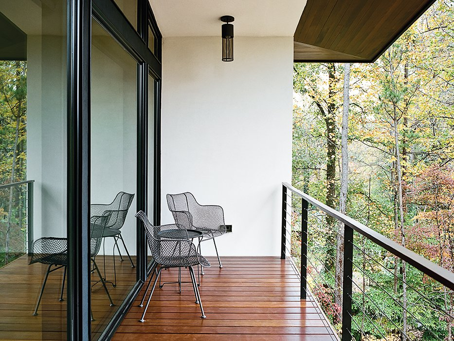 Wire chairs by Rejuvenation and pendants by Hinkley Lighting grace the balcony outside. Tagged: Outdoor, Small Patio, Porch, Deck, and Wood Patio, Porch, Deck.  Photo 12 of 13 in Minimal North Carolina Home Built for a Tech-Forward West Coast Couple