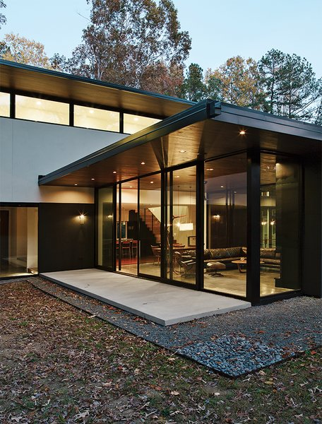The Clark family residence in Raleigh, North Carolina, was designed around the Series 600 multi-slide window walls from Western Window Systems, a rarity in the southeast.  Photo 2 of 13 in Minimal North Carolina Home Built for a Tech-Forward West Coast Couple