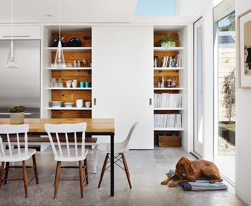 Featuring reclaimed wood from the original house, a single sliding door covers only half of the kitchen pantry. As the door slides, china and glassware are revealed on one side; the other side holds Anne's design library and favored heirlooms. The sliding door follows a track installed in the concrete underfloor; the shelves are supported by recessed steel brackets, strong enough to hold the weight of a man—or a baby. An additional full-size pantry is located inside the laundry room, toward the original bungalow. Tagged: Dining Room, Concrete Floor, Chair, Pendant Lighting, and Table.  Photo 9 of 12 in 1920s Bungalow Plus Modern Addition Equals Perfect Austin Home