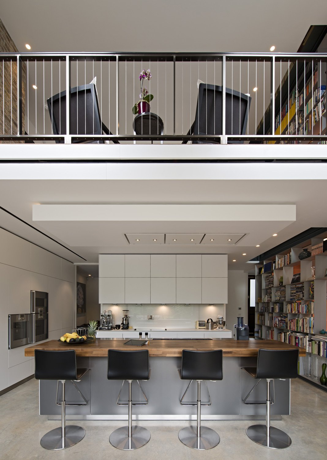The kitchen, Bulthaup island, and overhanging entrance-level comprise the remainder of the extension. A five-story double-sided, weld-free aluminum bookcase begins in the kitchen and rises through the lounge. A staircase traces every inch of it so that material can be readily accessed. A Spotlight on 10 Traditional Homes with Modern Interiors - Photo 17 of 21