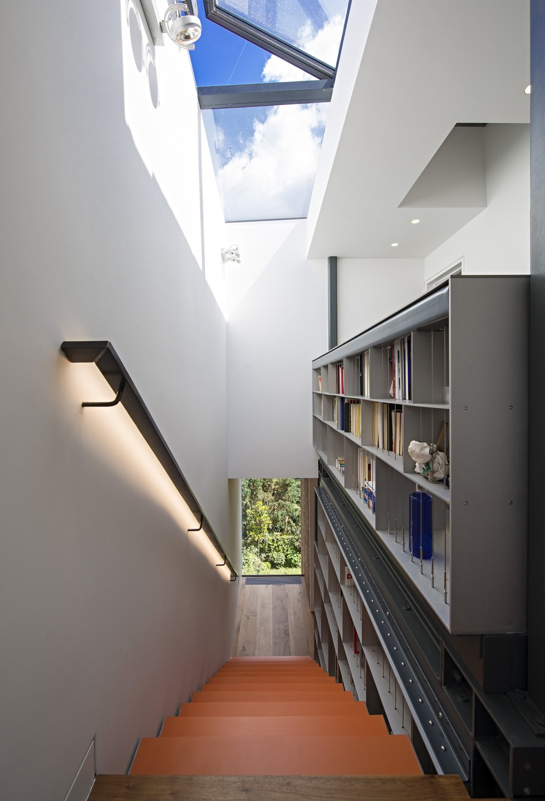Reaching for the skylight, the five-story staircase is met at the top by the custom bookcase. The skylight opens and closes automatically in response to temperature and weather. This integrated structure is the spine of the house, off of which all other spaces are arranged.  190+ Best Modern Staircase Ideas by Dwell from This Dramatic London Renovation Boasts a Five-Story Bookcase