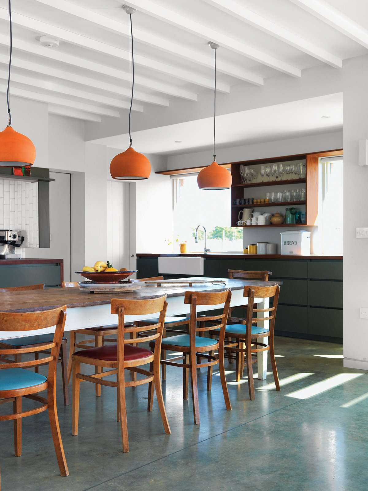 Above the dining room's Hodgson & Barker Antiques table—found on eBay—are ceramic pendant lights from Hand & Eye Studio. The architect acquired the wood chairs secondhand.  Photo 4 of 7 in Centuries-Old Farmhouses Inspired This Timeless Home