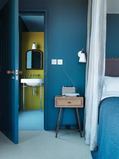 These 9 Spaces Show How to Rock a Monochromatic Color Scheme - Photo 1 of 9 - A blue-hued bedroom in a farmhouse that architect Lucy Marston designed for her family plays with shades of blue carpeting and textured fabrics (like the linen curtains and patterned blanket) to lighten the darker color of the walls, door, door frame, and baseboards. A shock of yellow in the bathroom beyond provides just the right amount of contrast.