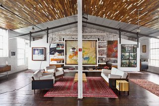 A Design Duo Takes Over A Whole Factory - Photo 3 of 7 - Beneath a recycled-wood ceiling and centered by a Bokhara rug, the living area contains furniture of their own design.