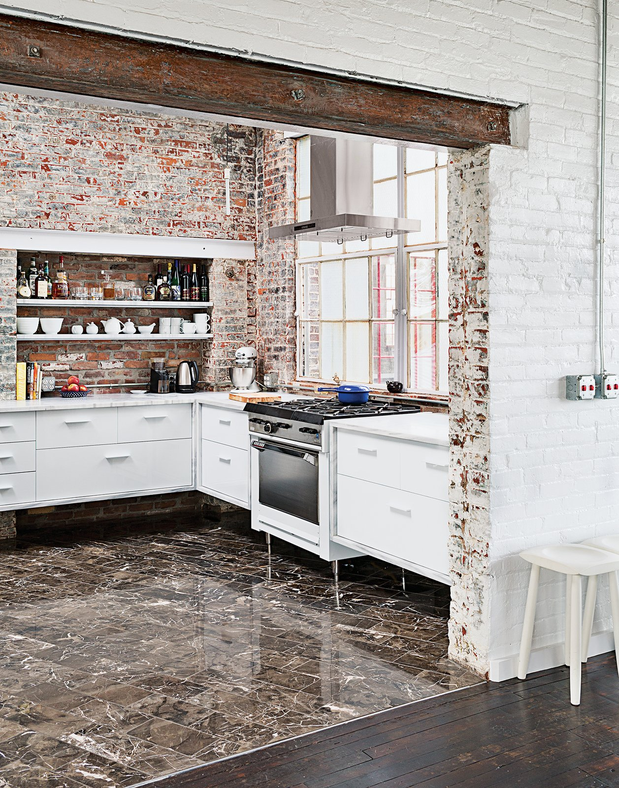 Among the couple's cost-saving measures was outfitting the kitchen with their own custom cabinetry. The brick and windows are original, the Garland stove was a Craigslist find, and the floor tile was found on closeout at a cost of about $1 per square foot.  20+ Modern Warehouse and Garages Conversions by Zachary Edelson from A Design Duo Takes Over A Whole Factory