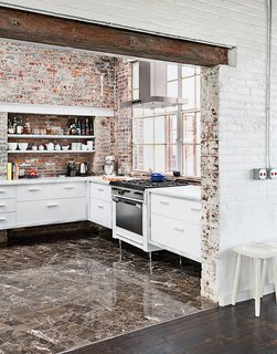 A Design Duo Takes Over A Whole Factory - Photo 2 of 7 - Among the couple's cost-saving measures was outfitting the kitchen with their own custom cabinetry. The brick and windows are original, the Garland stove was a Craigslist find, and the floor tile was found on closeout at a cost of about $1 per square foot.