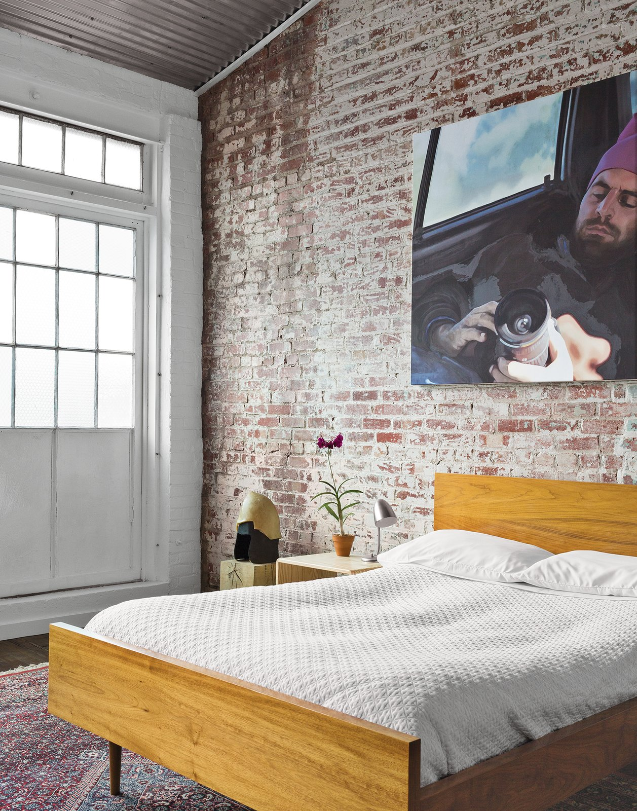 In the guest bedroom, a painting by Monique Crine hangs on the original brick wall above a Miles & May bed and side table. The rug is from ABC Carpet & Home. Tagged: Bedroom and Bed.  20+ Modern Warehouse and Garages Conversions by Zachary Edelson from A Design Duo Takes Over A Whole Factory