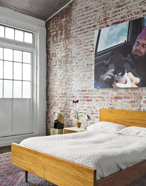In the guest bedroom, a painting by Monique Crine hangs on the original brick wall above a Miles & May bed and side table. The rug is from ABC Carpet & Home.