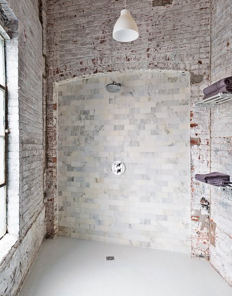 "The bathroom evokes the building's industrial bones. The pendant light is from Ikea, and the towel racks are repurposed train car luggage racks. The Carrara tiles are mismatched seconds. ""It works if you let yourself not try to fix it,"" says Brandon."