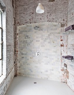 """The bathroom evokes the building's industrial bones. The pendant light is from Ikea, and the towel racks are repurposed train car luggage racks. The Carrara tiles are mismatched seconds. """"It works if you let yourself not try to fix it,"""" says Brandon."""