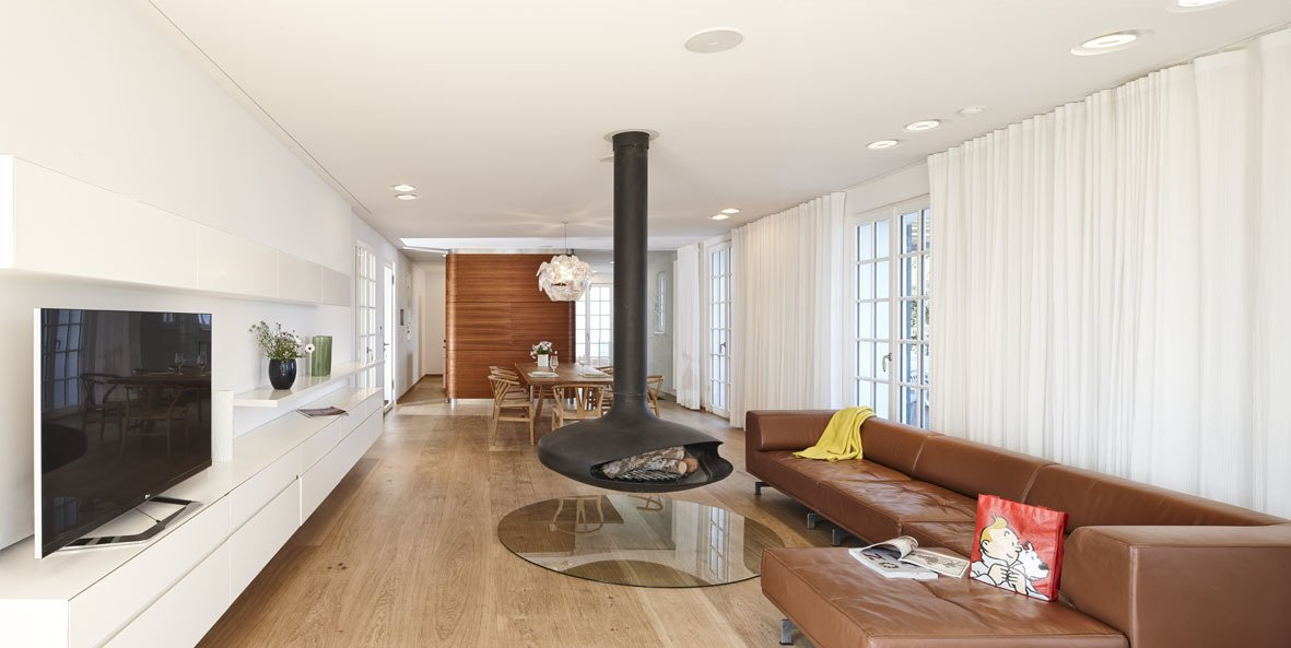 One of the biggest parts of the remodel was removing walls on the ground floor to make space for more of an open plan. The hanging steel Gyrofocus Fireplace by Focus gives the living room a unique character. It's flanked by a Delphi sofa from Erik Jørgensen.  Photo 10 of 10 in 10 Modern Renovations to Unique Homes in France