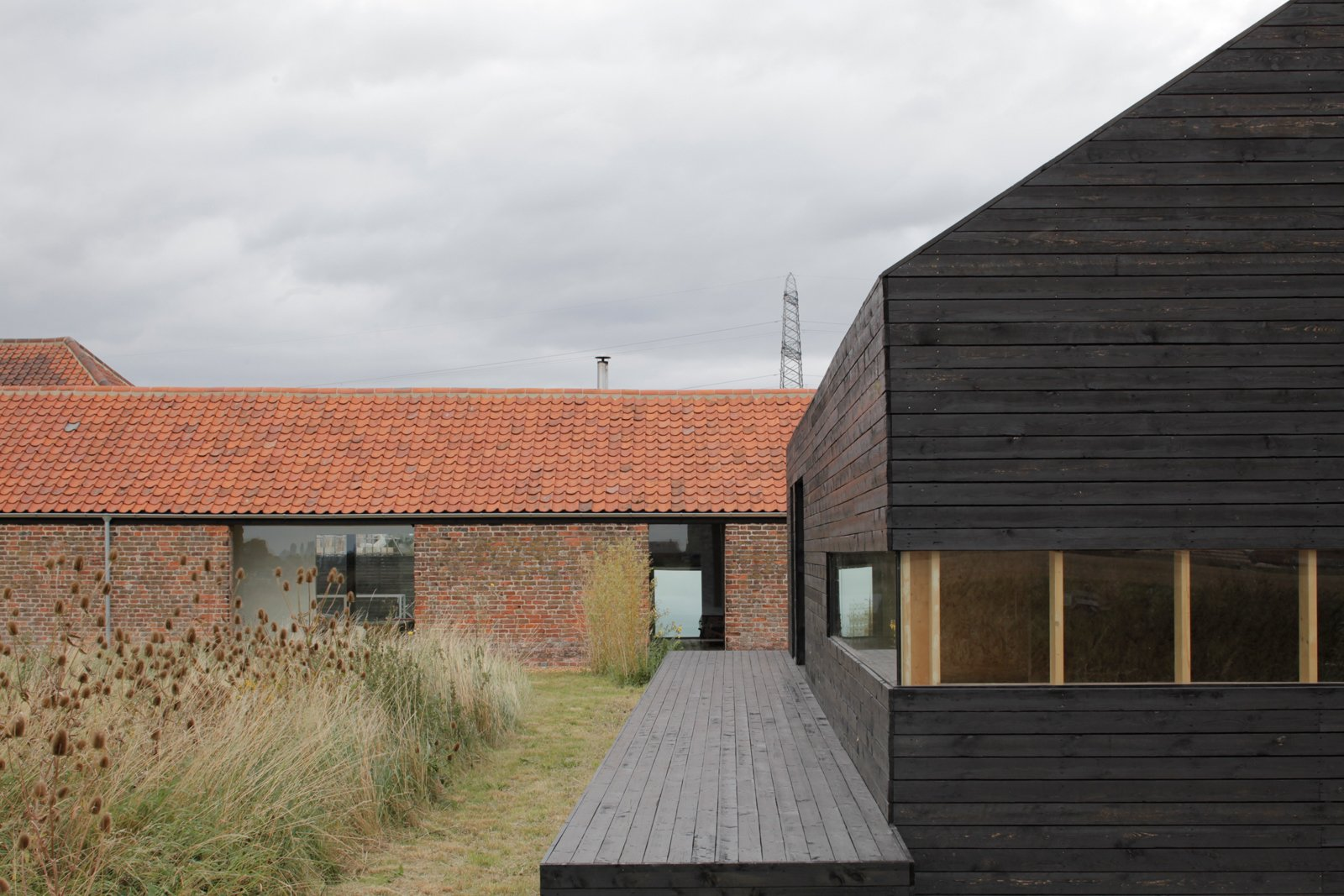 For a bit of elevation in the overwhelmingly horizontal compound, step onto the deck of the Stealth Barn. A strip of mowed grass delineates a path between the two structures; otherwise the grasses grow wild.  Composition by Lara Deam from A Pair of English Barns Hide Unabashedly Bold and Budget-Friendly Minimalist Interiors