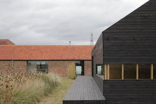 A Pair of English Barns Hide Unabashedly Bold and Budget-Friendly Minimalist Interiors - Photo 5 of 14 - For a bit of elevation in the overwhelmingly horizontal compound, step onto the deck of the Stealth Barn. A strip of mowed grass delineates a path between the two structures; otherwise the grasses grow wild.