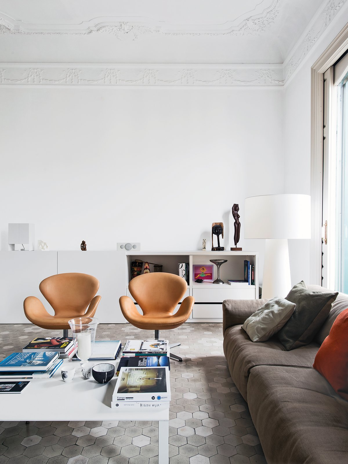 In the living room of the Barcelona apartment designer Elina Vila D'Acosta-Calheiros shares with her husband, Ginés Gorriz, Arne Jacobsen Swan chairs join a sofa by Piero Lissoni for Living Divani. The cabinet is from Cappellini, as is the Marcel Wanders Big Shadow lamp. Tagged: Living Room, Chair, Sofa, and Coffee Tables.  Photo 10 of 13 in 12 Creative Ways to Use Tile in Your Home from Meet Marcel Wanders, 2015 Dwell on Design Keynote Speaker