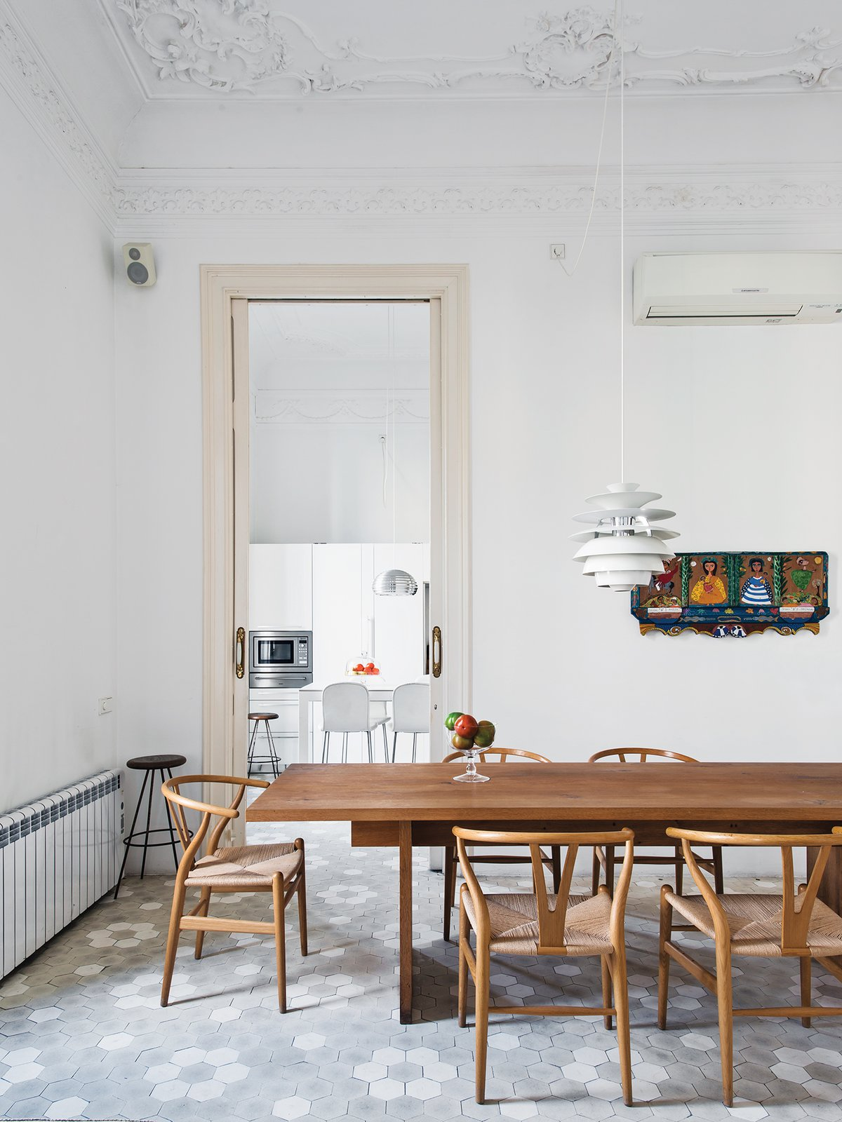 In the dining room, a Poul Henningsen lamp hovers over a table by Philipp Mainzer for E15, surrounded by Hans Wegner Wishbone chairs. The artwork is by Maria Sanchez. The designer added a Banco kitchen by Dada with Jasper Morrison stools. Tagged: Dining Room, Chair, Table, Pendant Lighting, and Porcelain Tile Floor.  Photo 22 of 41 in 50 Dashing Dining Rooms from Love at First Sight