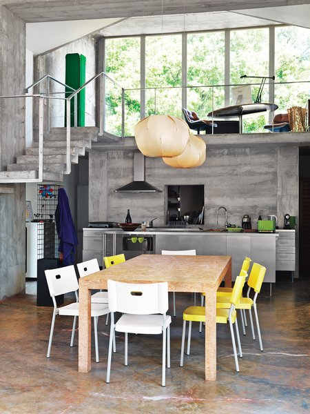 In the kitchen, a custom composite dining table is paired with bright plastic Ikea chairs. Crasset's Evolute pendant lights for Danese Milano, with origami-esque folded shades in maple veneer, hang above.