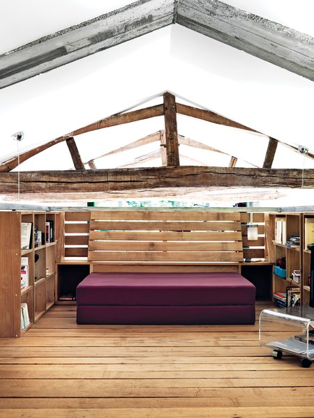 In the newly created box-shaped balcony, which hovers above the double-height living room, oak built-ins complement the home's original timber beams (above).