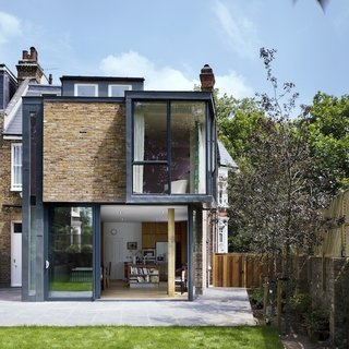 10 Indoor-Outdoor Homes in London - Photo 7 of 10 - For the Milman Road renovation, the team at Syte Architecture referenced the past while assembling the two-story addition, cladding the exterior in zinc and reused brick from the original wall so it blended with the express chimneys and surrounding structures.