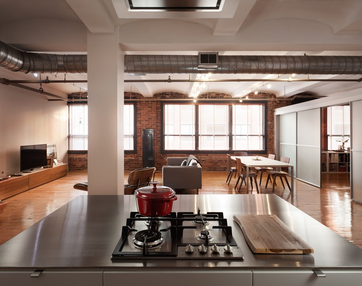 "The building was built in 1910. ""It's a pretty raw space with rough exposed brick, barrel vaulted ceilings, original hardwoods, and exposed ducting,"" Greenawalt says. ""We tried to use industrial materials—stainless steel, perforated steel, brick—in a more refined way for the kitchen."" Tagged: Kitchen and Cooktops.  Loft by David Christopher Kinikin from Clever Red Pegboard Backsplash in a Remodeled Kitchen"