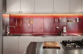 12 Brilliant Kitchen Backsplash Ideas - Photo 1 of 12 - At a Boston loft in a former textile factory, Bunker Workshop created a minimal, efficient kitchen that features a red steel pegboard backsplash. Now that cooking utensils are easily accessible, the homeowner is able to prepare meals efficiently.