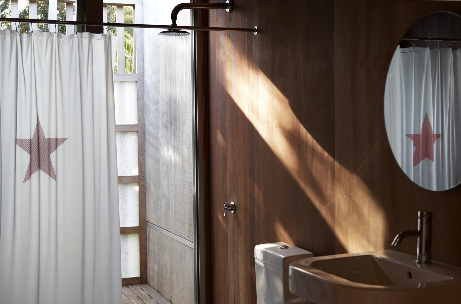 The cedar plywood paneling used throughout the project adds a mellow quality to the light. The dropped fiberglass screen recalls an outdoor shower, but also provides privacy.  The materials were chosen for their texture, weathering characteristics, durability, and organic appearance — while fiberglass may not actually be natural, says architect Lance Herbst, the type used here, with its visible fibers, has a natural quality.  The basin is Metrix, and the shower curtain by Catherine David. Tagged: Bath Room and Full Shower.  Photo 2 of 7 in Off-the-Grid Island House in New Zealand Connects with the Outdoors