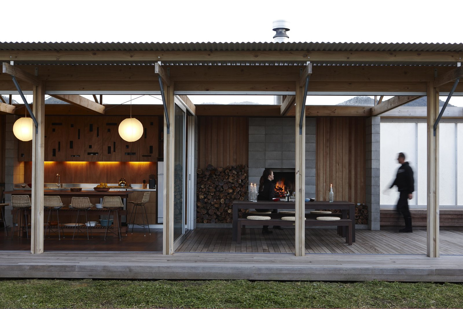 """The bach features a series of moveable wall-sized glass panels and screens that define light, shade, and shelter, and are designed to make the most of the limitations of the surrounding plot. The central kitchen-dining-living space can be opened completely, or shut up tight in winter.  """"One of the builders referred to it as the 'inside-out house',"""" says Herbst. """"I thought that was quite fitting.""""  Photo 4 of 7 in Off-the-Grid Island House in New Zealand Connects with the Outdoors"""