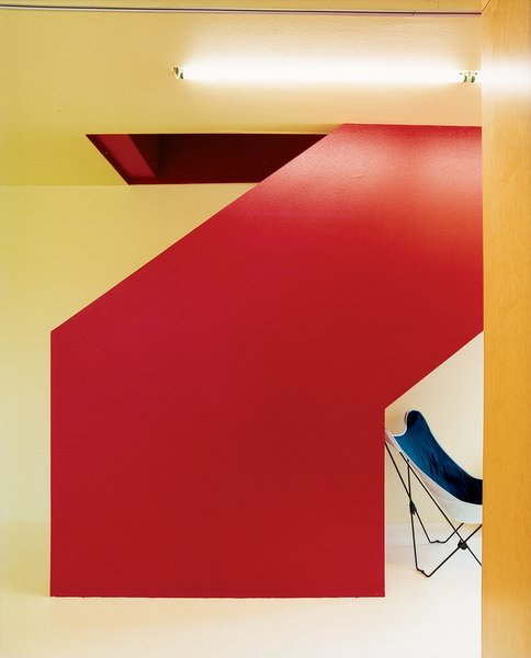 The stairwell is the bright core of the house. To keep an open feeling, and costs down, it zigzags its way up. Inexpensive metal railings are set inside and painted the same red to disappear into the stairwell.