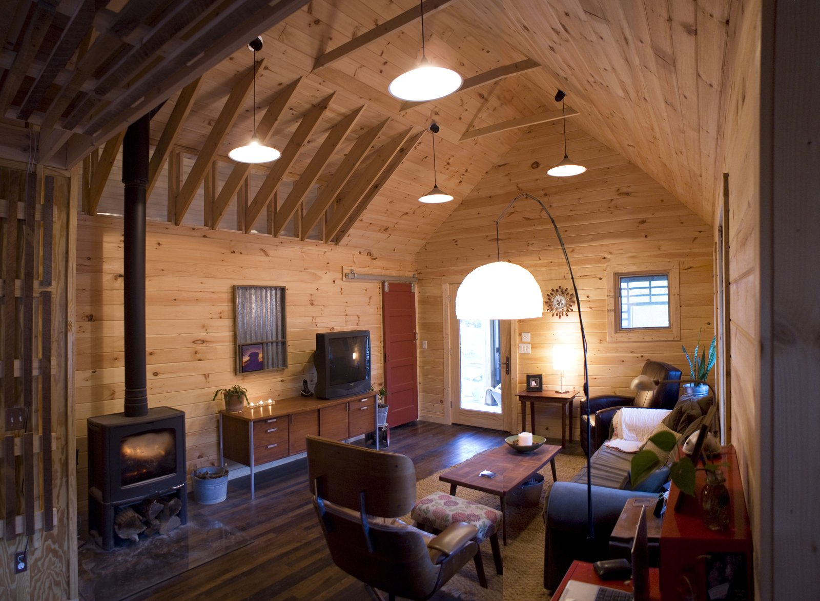 Inside the main living area, tongue-and-grooved white pine covers the walls and vaulted ceilings, and a red closet door, built of salvaged pine from the original house, slides open and closed on barn track hardware. 20 Modern Living Rooms - Photo 5 of 20