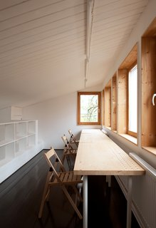 A Compact Home in Moscow Built on the Lowest Possible Budget - Photo 9 of 9 - Near custom pine shelving on the third floor, folding chairs and a table from IKEA provide a tranquil space for studying.
