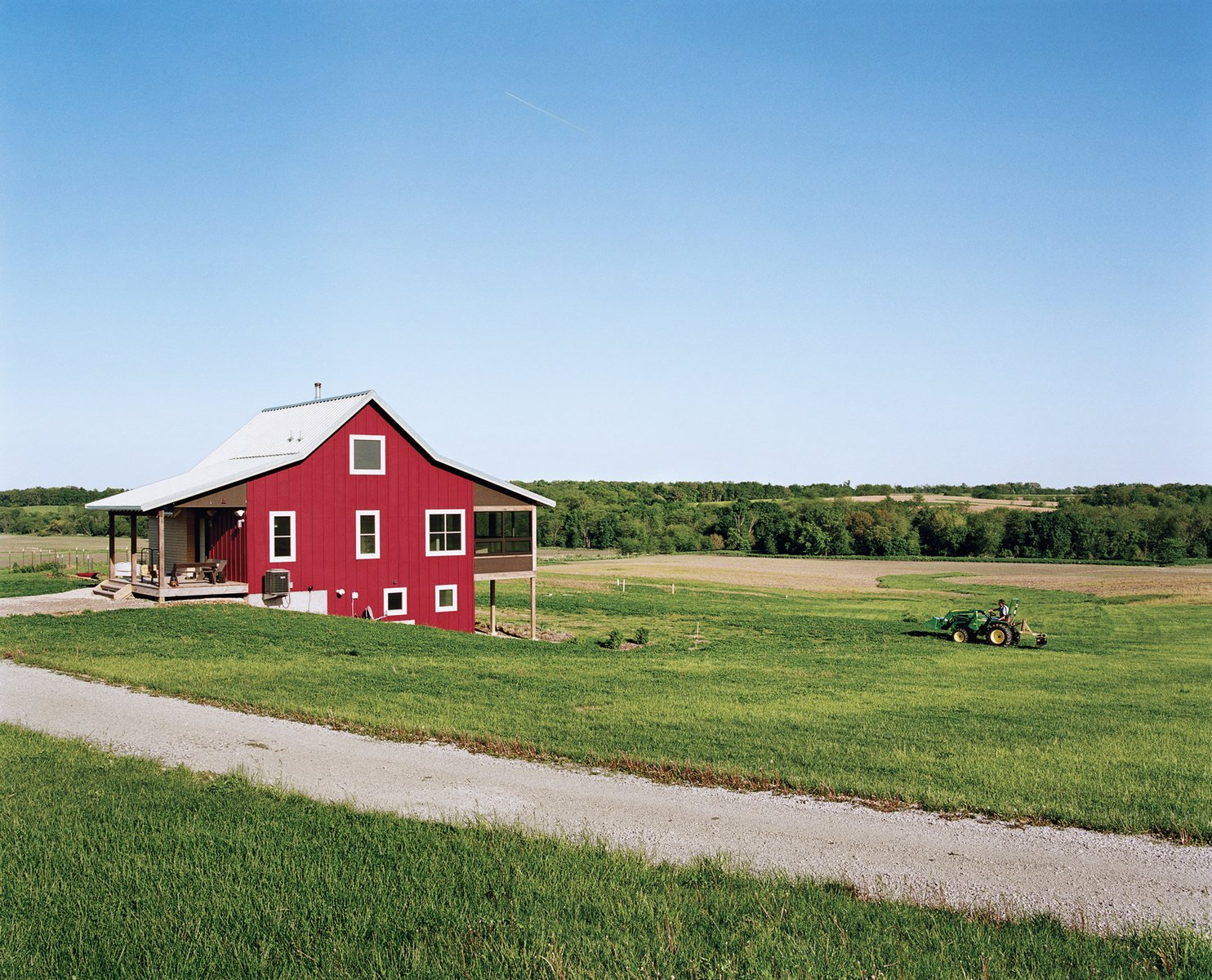 Geoff and Joanna Mouming's compact modern farmhouse is the first permanent structure at Yum Yum Farm in Wellman, Iowa. On the field that stretches out before it, organic vegetables will soon make attentive farmers of the Moumings. Photo by: Mark Mahaney  Photo 1 of 9 in The Eco-Friendly Guide to Upgrading an Existing Home from Modern Homes Across the American Midwest