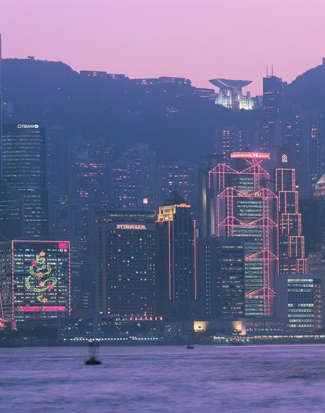 The Hong Kong skyline, including the HSBC building designed by Foster + Partners (foreground) and the Peak Tower designed by Terry Farrell (illuminated at top). Image courtesy of the Royal Institute of British Architects.