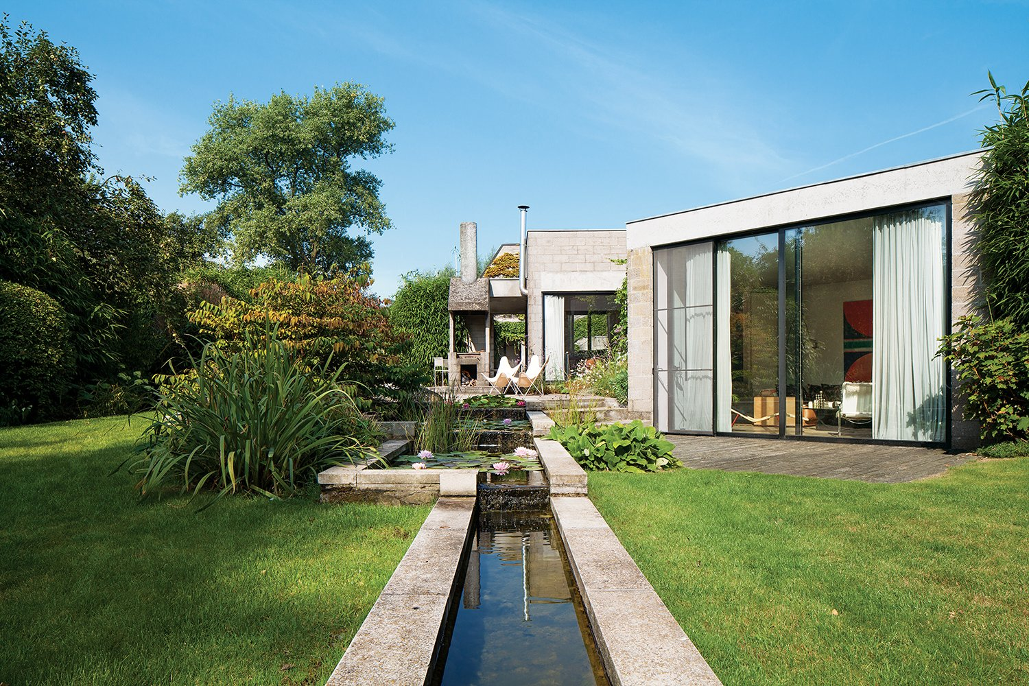 When Belgian fashion retailer Nathalie Vandemoortele was seeking a new nest for her brood, she stumbled upon a fortresslike house in the countryside designed in 1972 by a pair of Ghent architects, Johan Raman and Fritz Schaffrath. While the Brutalist concrete architecture and petite but lush gardens suited her tastes to a tee, the interiors needed a few updates. Tagged: Grass, Trees, Back Yard, Exterior, House, and Concrete Siding Material.  Concrete by Brandon Armstrong from A Concrete Home in Rural Belgium