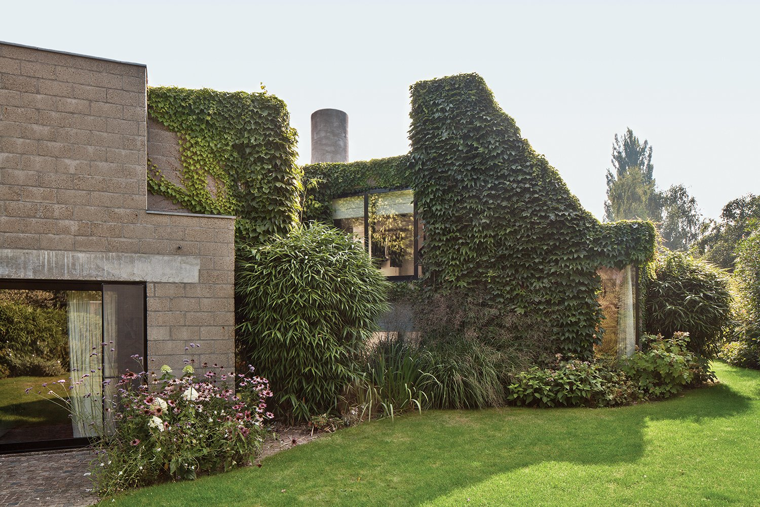 """This house is actually quite demanding; you have to be committed.""—Resident Nathalie Vandemoortele Tagged: Outdoor, Back Yard, Trees, and Grass.  Photo 3 of 9 in A Concrete Home in Rural Belgium"