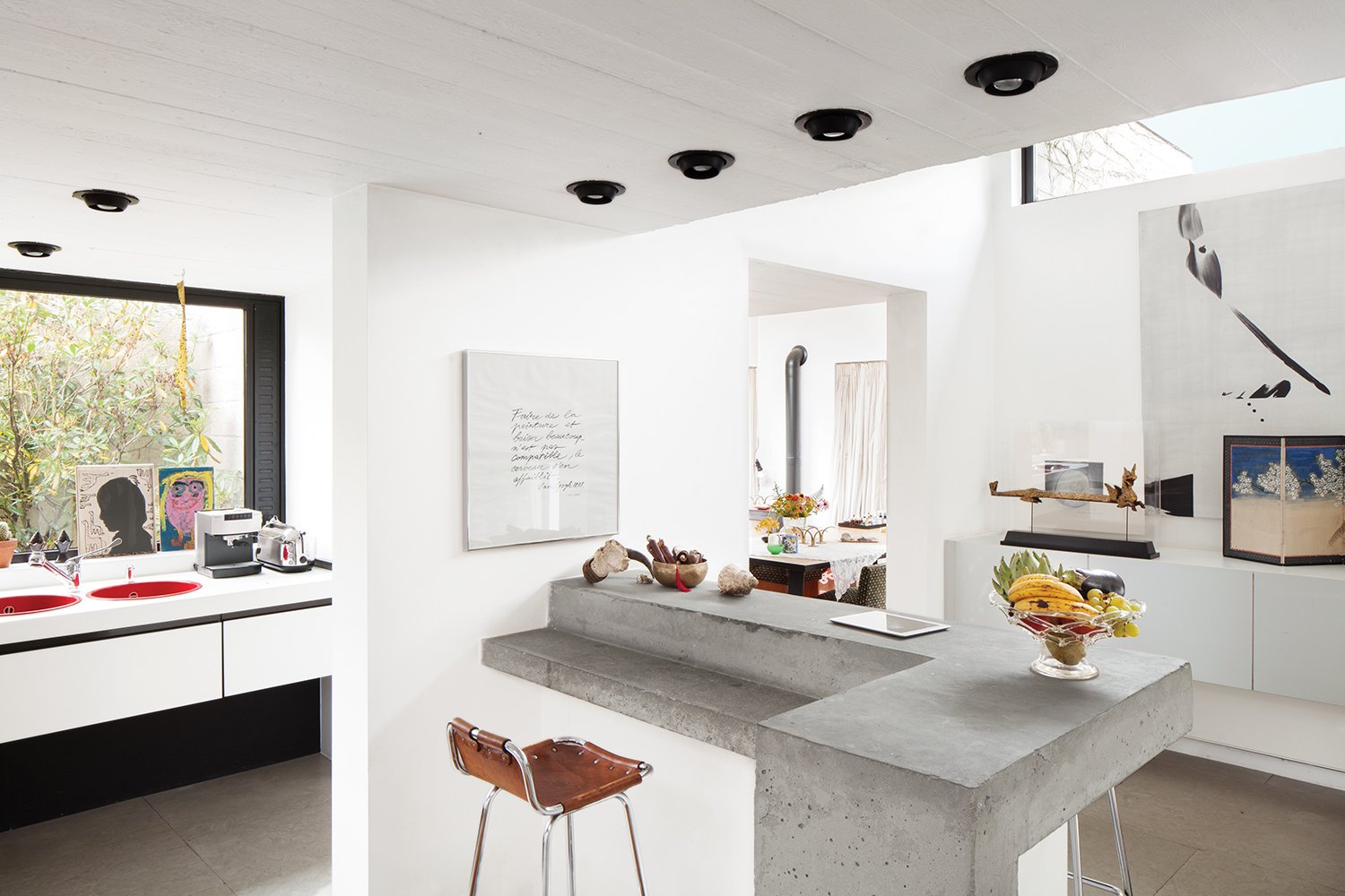 Vandemoortele worked with designer Renaud de Poorter on the interior renovations, which included opening up the heavy structure with the help of new windows and doors to the outside. They didn't want to gut the space, and kept existing decorative motifs like the dining room's circa-1975 painted cupboard. Tagged: Kitchen, Concrete Counter, and Recessed Lighting. A Concrete Home in Rural Belgium - Photo 4 of 9
