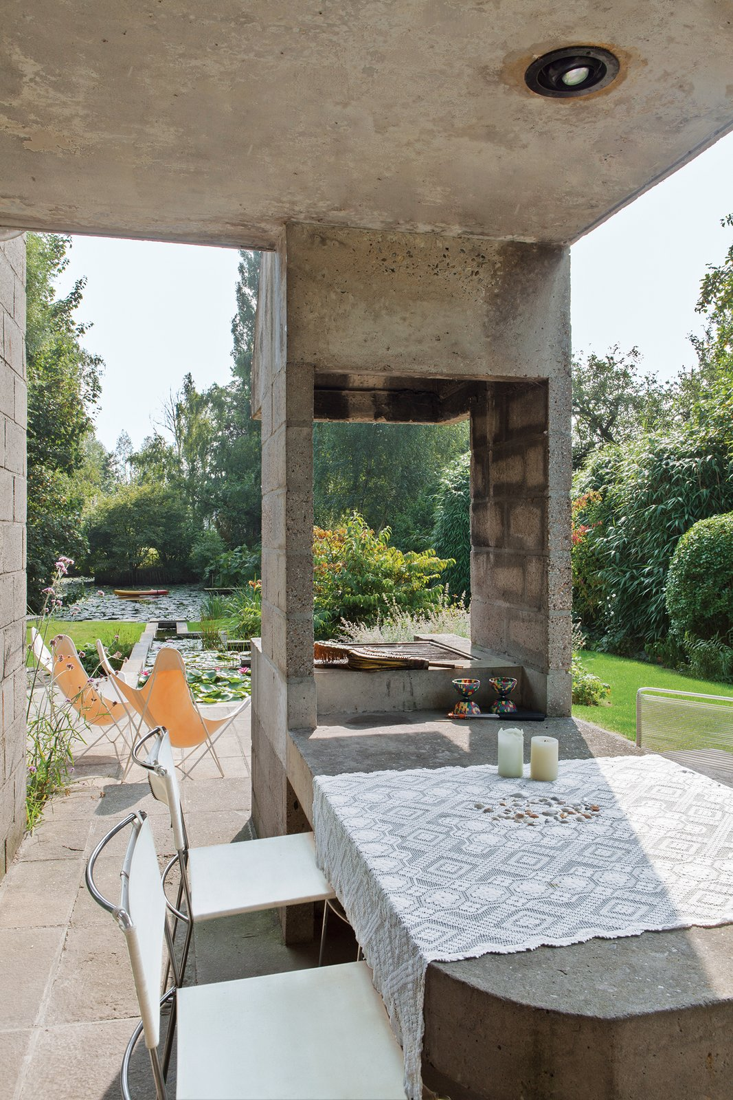 The dining room leads onto a terrace with a built-in concrete table and barbecue that are original to Raman and Schaffrath's design. A pair of Hardoy butterfly chairs from Knoll are positioned by the pond.