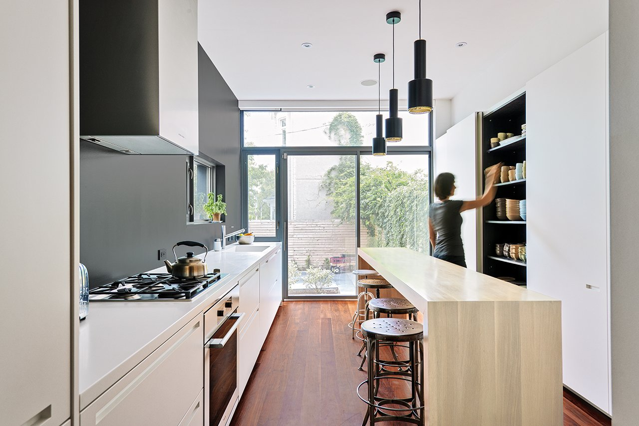 The architects knocked out the kitchen's back wall, where a single window had formerly let in a miniscule amount of light, and installed sliding glass doors instead. A soothing charcoal accent wall anchors the bright white cabinetry and Corian countertops, while pendant lights by Alvar Aalto hang above an oak island. The fixtures are from KWC, Dornbracht, and Catalano.
