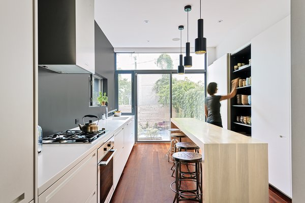 The architects knocked out the kitchen's back wall, where a single window had formerly let in a miniscule amount of light, and installed sliding glass doors instead. A soothing charcoal accent wall anchors the bright white cabinetry and Corian countertops, while pendant lights by Alvar Aalto hang above an oak island. The fixtures are from KWC, Dornbracht, and Catalano. Photo 3 of Contrast House modern home