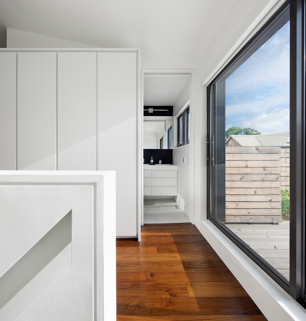 "Directly at the top of the stairs on the third story, oversized sliding glass doors lead out to a sunny roof deck. To the left, an ensuite bathroom is furnished with Duravit and Wetstyle fixtures. ""It has tiny white tumbled marble mosaic tiles, which are very soft underfoot,"" Dubbeldam says.  Contrast House by Laura C. Mallonee"