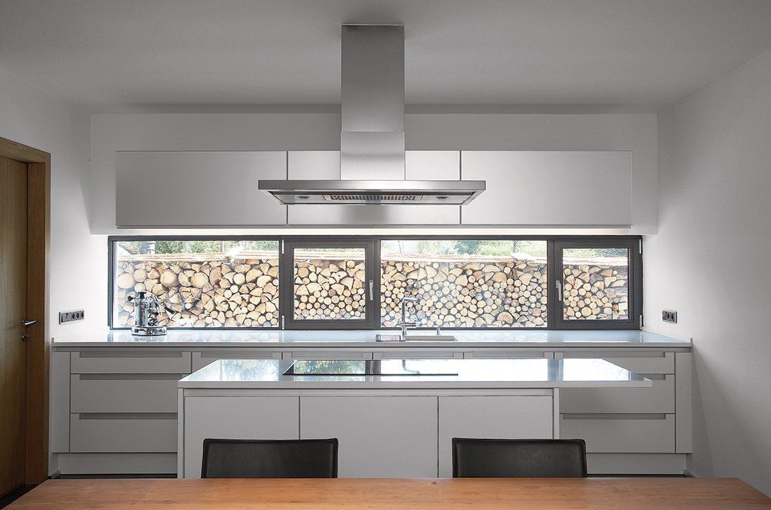 In the kitchen, symmetrical, glossy surfaces keep the eating area clean. Tagged: Kitchen and Range Hood.  Photo 4 of 4 in A Striking Bohemian Geothermal Home