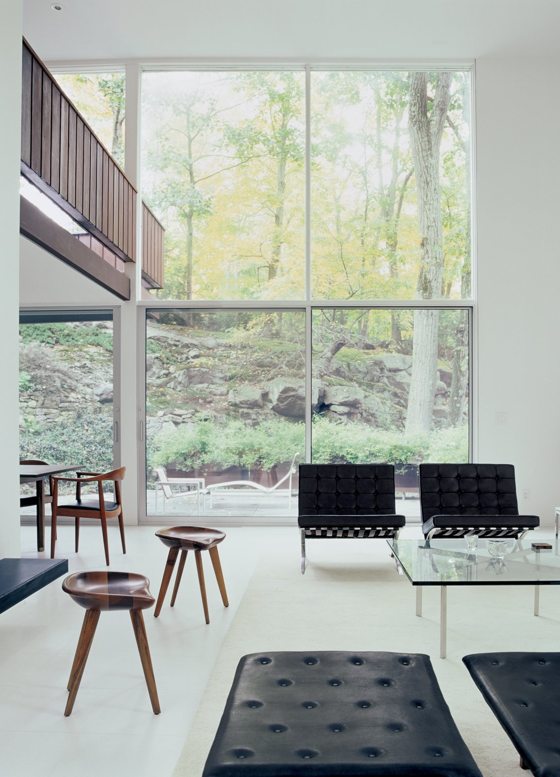 """The second-floor bridge that leads to the front door flows from the outside in. """"Tractor seat"""" stools designed by Bassam perch on a floor of pristine white terrazzo. Tagged: Living Room, Chair, and Porcelain Tile Floor.  Photo 3 of 6 in Pursuing Perfection"""