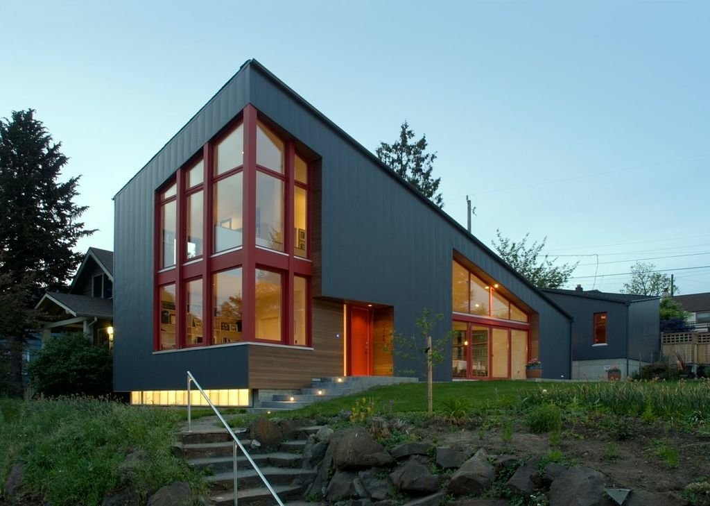 At the lower left, polycarbonate panels glow under the cantilevered, vertically-seamed sheet-metal facade.  Photo credit: Dale Christopher Lang PhD AIAP  Photo 1 of 5 in Angular Multi-Generational Home in Washington