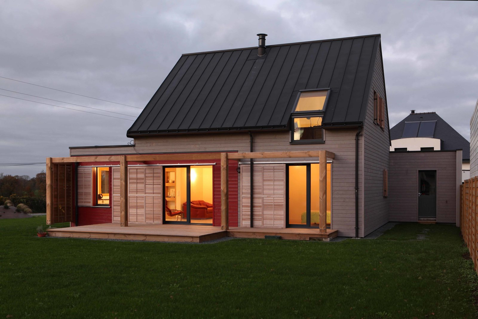 The roofs of each of the three sections of the home are constructed of zinc and are insulated for added protection. Tagged: Outdoor, Grass, Wood Patio, Porch, Deck, Back Yard, and Small Patio, Porch, Deck.  Roofs by Aileen Kwun from A Cozy, Well-Sealed Cottage in Northwest France Goes Green