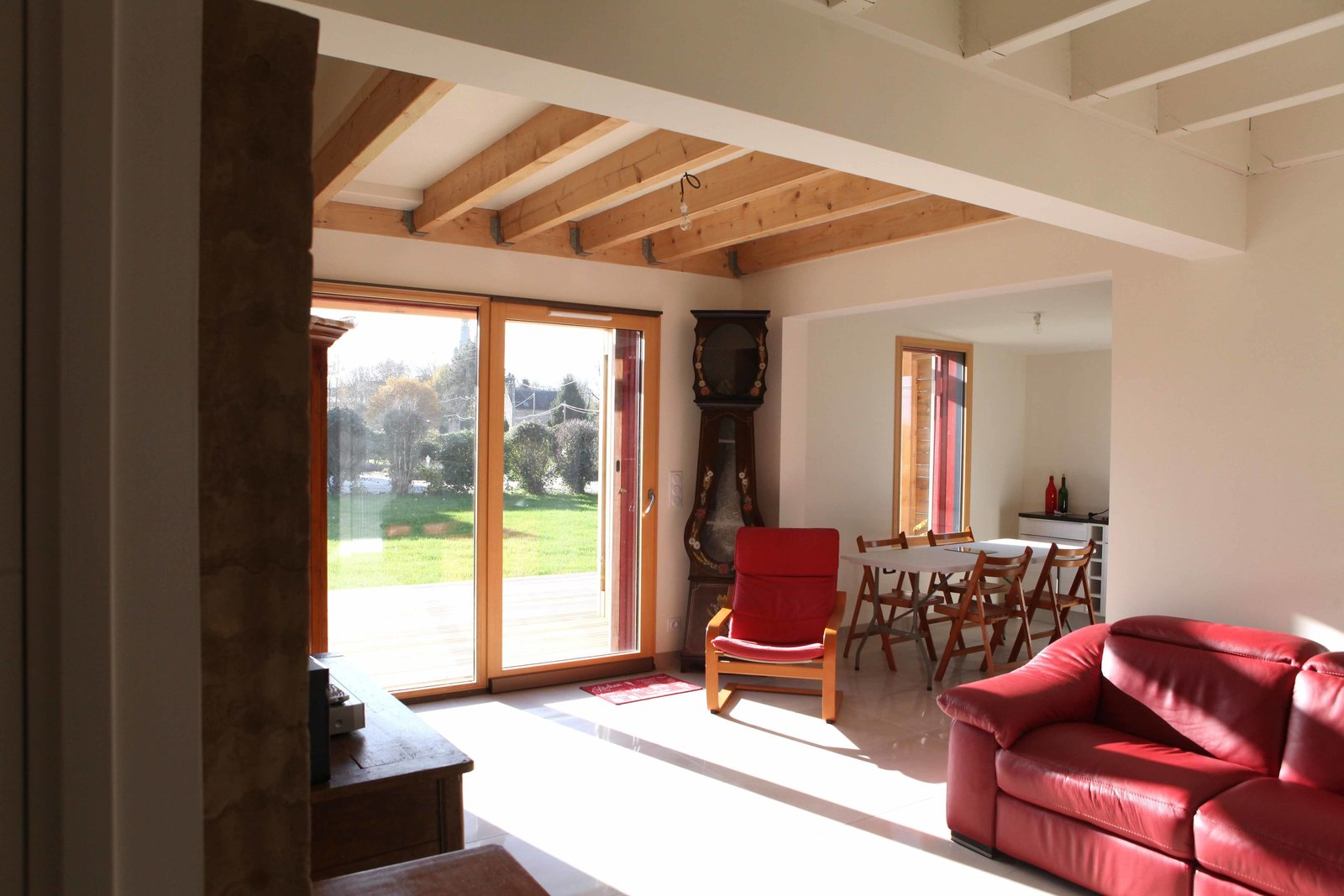 The main volume of the structure houses a ground-level living space and a bedroom as well as a lofted bedroom, bathroom, and study above. Exposed beams and natural light provide rustic charm.  Photo 3 of 7 in A Cozy, Well-Sealed Cottage in Northwest France Goes Green