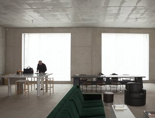 """First his studio, then his home. David Chipperfield chose Berlin, after the city commissioned him to rebuild the Neues Museum in 1997. It is in the same neighborhood, Mitte. In the courtyard that contains both his house and his studio, Chipperfield also designed a canteen, a place where locals meet. The house is built of concrete, with large windows overlooking the street and the courtyard. It contains a few '50s and '60s Italian furnishings, and two colours. The green of a velvet sofa and the orange of a bookcase that divides the space between the kitchen and the sitting room."""