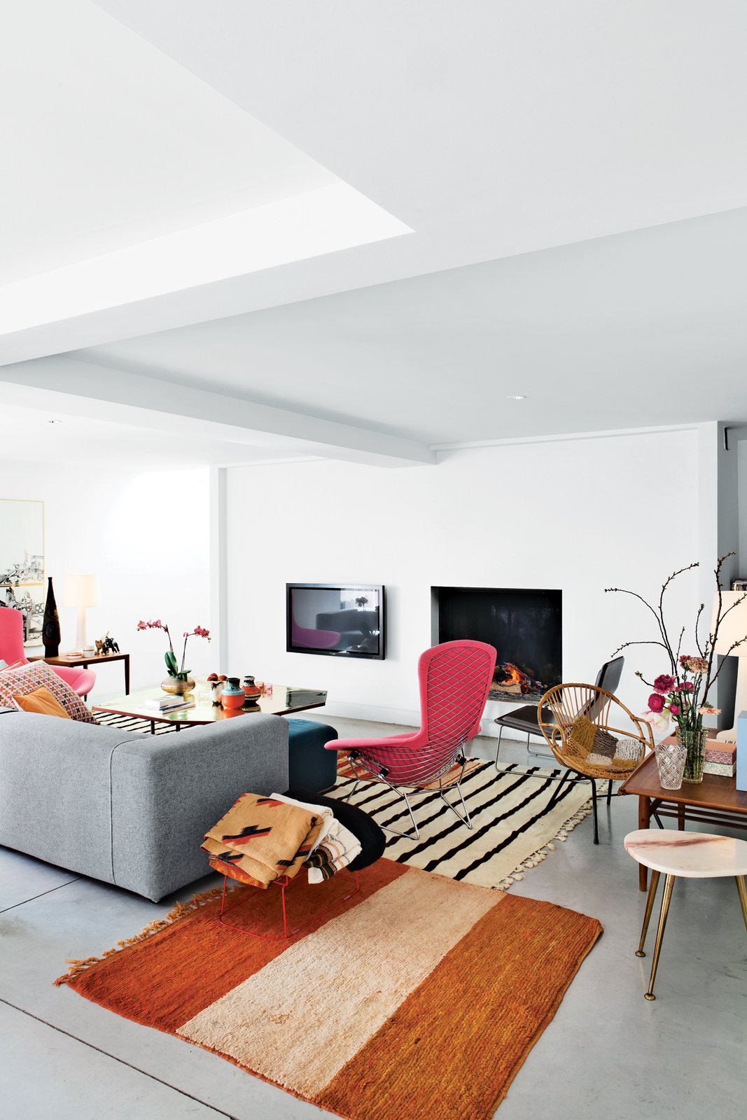 A pair of interior architects with a years-in-the-making furniture collection recast an old Belgian factory—in Bellem, a 25-minute drive out of Ghent and halfway to Bruges—as a playful family home. The stars of the living room are a pair of pink Bird chairs by Harry Bertoia for Knoll, accented by a brass-and-steel coffee table designed by homeowners as well as vintage marble-topped and wood occasional tables and antique rugs are from Morocco. Photo by Frederik Vercruysse.  100+ Best Modern Seating Designs by Dwell from Design Classic: Bertoia Seating Collection