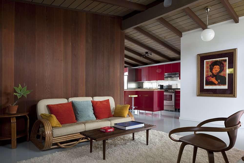 The existing partitions were tongue-and-groove redwood. To update the interior, each panel was painstakingly removed, refinished in a darker hue, and replaced. The centerpiece, a four-strand rattan couch, is complimented by other wooden pieces, like this original Cherner chair, also a Craigslist purchase. Tagged: Living Room, Sofa, Chair, and Rug Floor.  Photo 5 of 24 in A Cherner Chair Retrospective from Hillside House No. 3