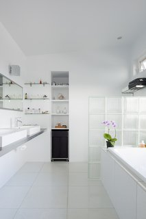 "5 Light-Filled Spaces That Use Glass Blocks Creatively - Photo 2 of 5 - In the interior of a bathroom in a Hawaiian renovation, patterned glass blocks are reused from a previous building and turned into a low, translucent partition providing light and privacy. With all white fixtures, a transom window, and a long mirror, light fills the space, even behind the glass block wall. <span style=""color: rgb(204, 204, 204); font-size: 13px;"">Photo by Olivier Koning</span>"