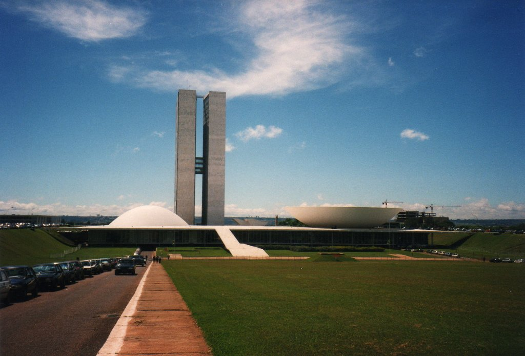 Brazilian National Congress   Brasilia, Brazil (1964)  One of Niemeyer's numerous contributions to Brasilia, the custom-built capital created out of thin air in the '60s, the National Congress building symbolizes the working of the legislative branch; two semicircles, one for the Congress and one for the Senate, are divided by twin office towers. Photo by David Holt. Design Icon: Oscar Niemeyer - Photo 2 of 10